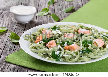 salmon and spinach fettuccine alfredo pasta on white dish on green table mat on a rustic with cream sauce on a gravy boat, italian style, close-up - stock photo