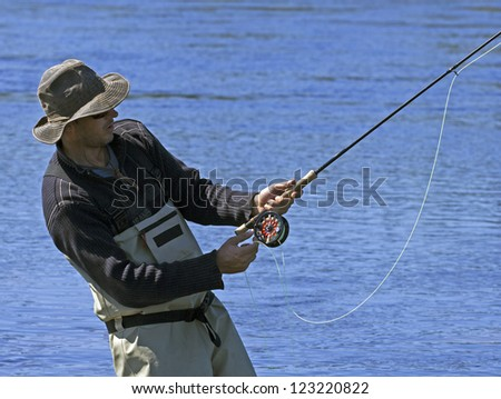 salmon angler in action on a river - stock photo