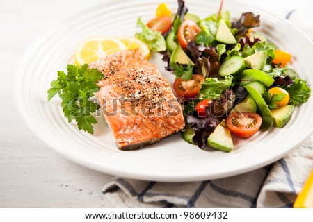 Salmon Baked and Served with Tomatoes, Cucumbers, Avocado, Greens - stock photo