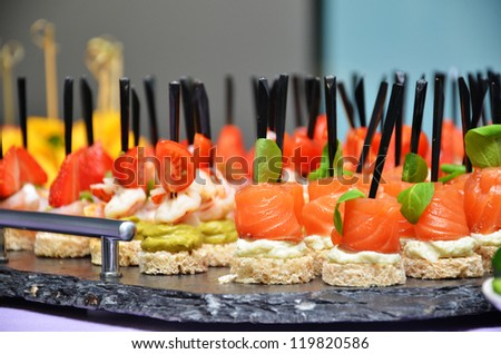 Salmon canapes with basil on tray. Small shallow DOF - stock photo
