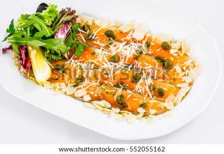 Salmon carpaccio with parmesan cheese, almond flakes and capers on white plate