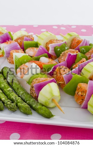 Salmon cubes and Shrimp complimented with vegetables on skewers. Ready to cook. Red onions, zucchini, green peppers and asparagus.