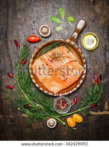 Salmon fillet in fried pan with herbs and ingredients for cooking on rustic wooden background, top view. Healthy food or diet nutrition concept - stock photo