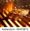 salmon fillet on the grill with flames closeup - stock photo