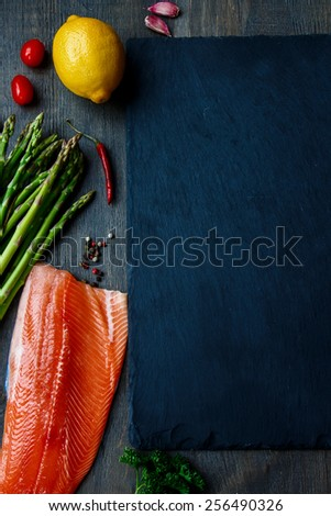 Salmon fillet with asparagus and aromatic herbs, spices and vegetables - healthy food, diet or cooking concept. Top view. - stock photo