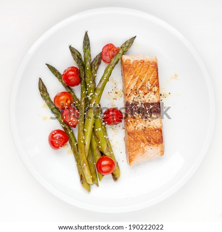 Salmon fillet with asparagus and cherry tomatoes on white plate - stock photo
