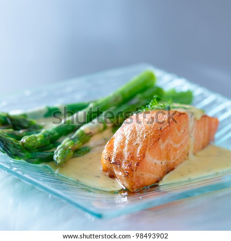 Salmon fillet with asparagus and yellow sauce on glass plate