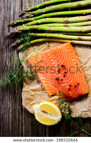 Salmon fillet with lemon, spices and asparagus - stock photo