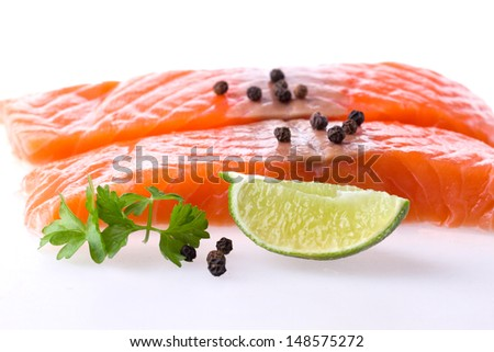 Salmon fillet with pepper, parsley and lime over white selective focus - stock photo