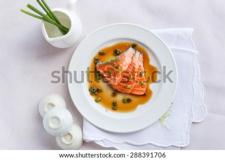 salmon fillet with sauce on white dish - stock photo