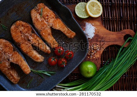 Salmon fillets fried in a pan and grill is ready for serving on vintage wooden board which has a green onion lemon and lime salt and pepper - stock photo