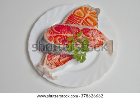 Salmon fillets on a white background with coriander leaves on top. Food and recipes themes