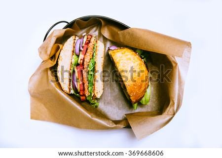 Salmon fish burger cut in two parts on white background. View from top. Isolated on white - stock photo