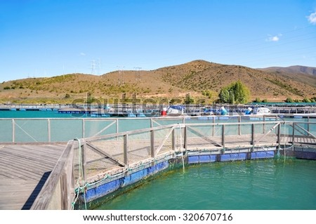 Salmon Fish farm floating on the glacial waters of Wairepo Arm, Twizel, South Island, New Zealand - stock photo