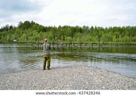 salmon fisherman casting out into river stream in summer