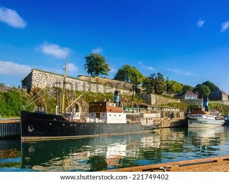 Salmon fishing boat in  harbor of Oslo fjord with Akershus fortress in background - stock photo