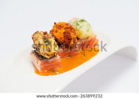 salmon garnish with three kinds of potatoes - stock photo