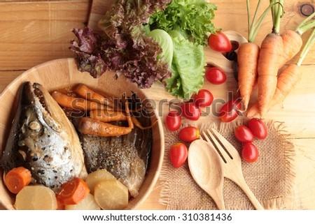 Salmon head cooked of tari yaki sauce with fresh vegetables - stock photo