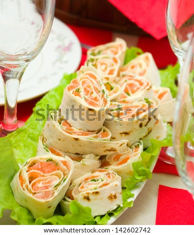 Salmon lavash rolls served with fresh salad leafs - stock photo