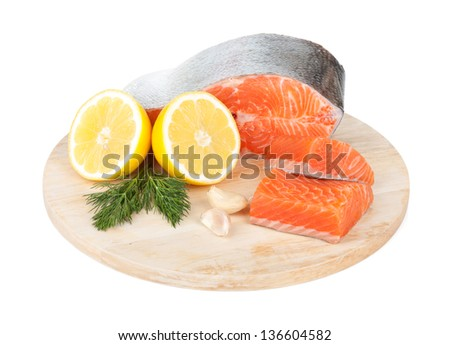 Salmon on cutting board with lemons and herbs. Isolated on white background - stock photo