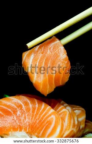 Salmon raw sashimi on black background  - stock photo