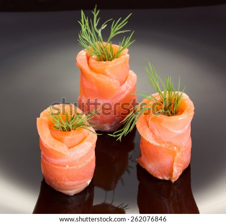Salmon rolls on black plate - stock photo