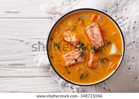 salmon soup with vegetables and thyme in white bowl. horizontal top view