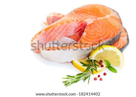 Salmon steak decorated with basil, lemon and rosemary on a white background. - stock photo