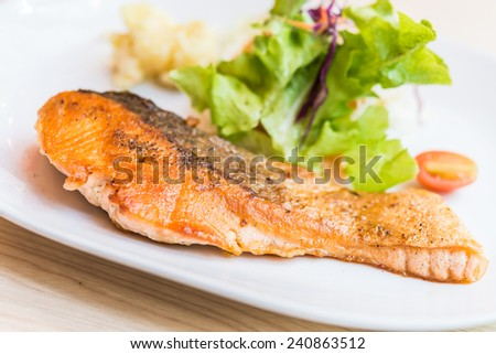 Salmon steak in white plate on wooden table