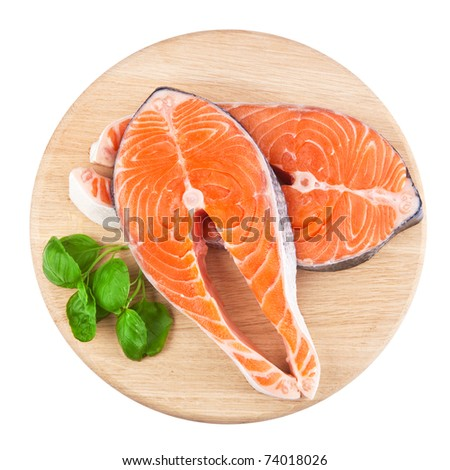 Salmon steak red fish decorated with basil on the kitchen board - stock photo