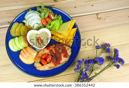 Salmon steak with breads, potato slice, green apple slice, red apple slice, onion slice and cabbage salad in blue plate decorate with purple flower on the wooden background - stock photo