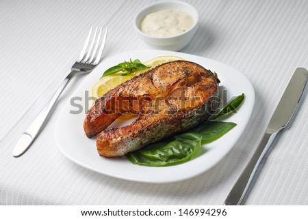 Salmon Steak with Lemon and Basil on white plate