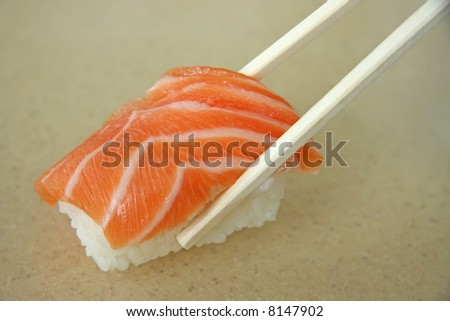 Salmon sushi held in chopsticks japanese cuisine