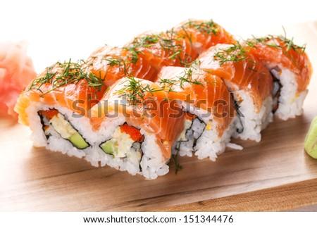 Salmon sushi rolls on wooden plate. - stock photo