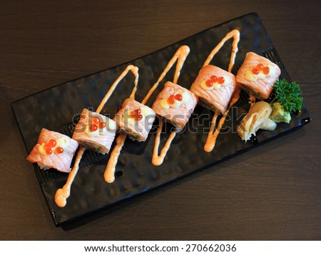 Salmon sushi rolls with spicy sauce on the plate - stock photo