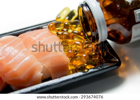 Salmon sushi served with fish oil pills poured from brown bottle isolated on white background - stock photo
