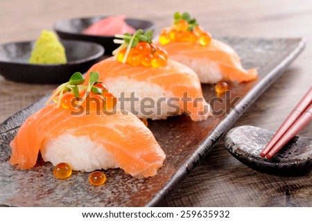 Salmon sushi with caviar and chopsticks - stock photo