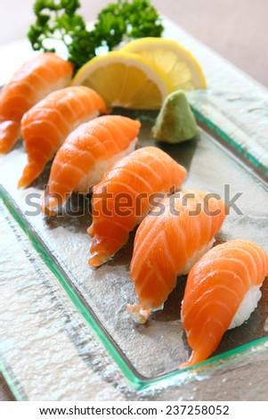 Salmon Sushi with wasabi on clear glass square dish