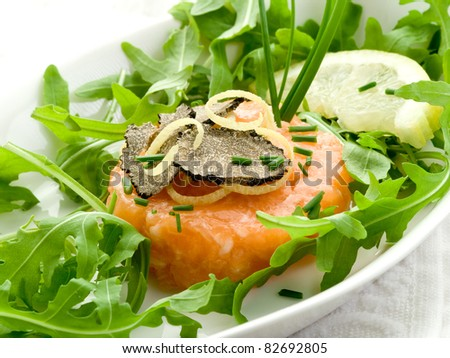 salmon tartar with truffle and arugula salad - stock photo