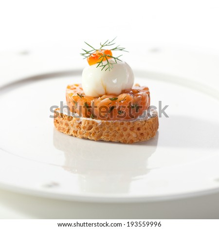 Salmon Tartare with Poached Quail Eggs and Caviar - stock photo