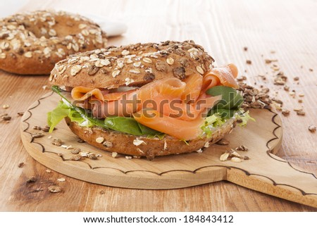 Salmon whole grain bagel on wooden kitchen board on wooden background. Traditional bagel eating. - stock photo