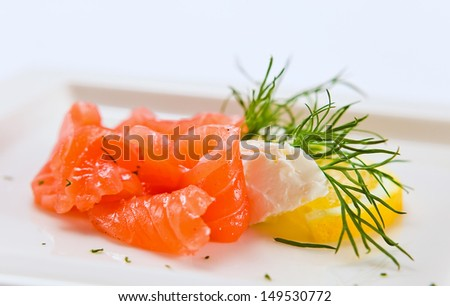 salmon with dill and lemon on a white plate - stock photo
