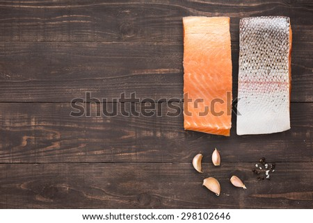 salmon with garlic on wooden background with a lot of copy space for your text or editing.  - stock photo