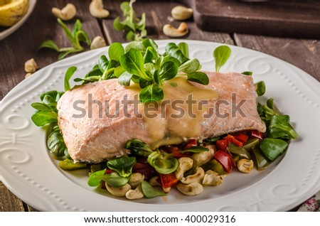 Salmon with hollandaise sauce and fresh salad with roasted walnuts - stock photo