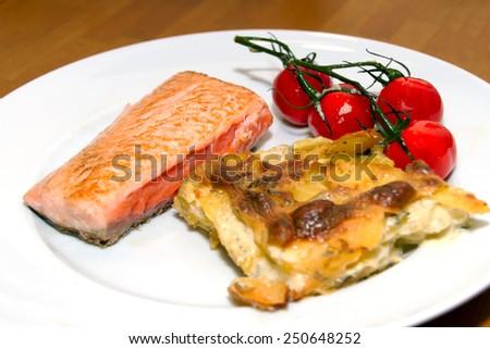 Salmon with potato gratin and tomatoes - stock photo