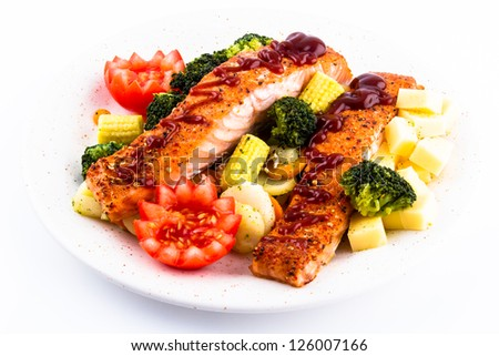 Salmon with tomato, broccoli, corn and cheese on a white plate seasoned with gravy