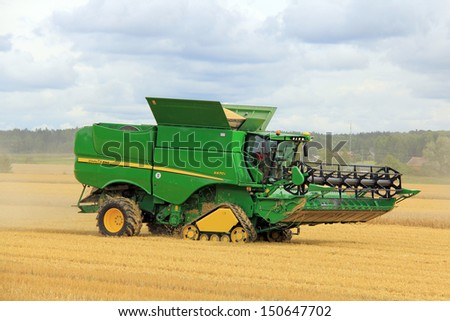 SALO, FINLAND - AUGUST 10: John Deere Combine s670i harvests barley at the annual Puontin Peltopaivat Agricultural Harvesting and Ploughing Show on August 10, 2013 in Salo, Finland. - stock photo