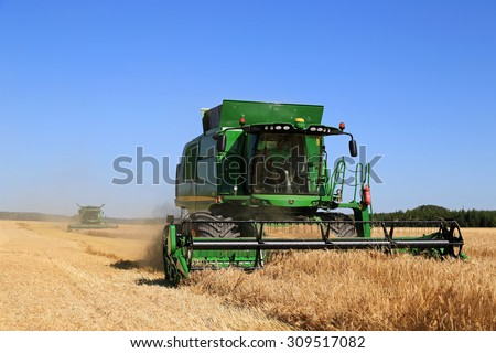 SALO, FINLAND - AUGUST 22, 2015: Two John Deere Combines T550 and s670i harvest barley at Puontin Peltopaivat Agricultural Harvesting and Cultivating Show. - stock photo