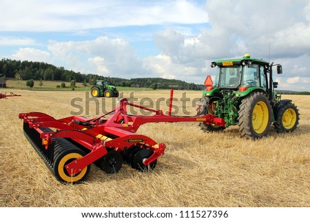 SALO, FINLAND - AUGUST 18:Vaderstad Carrier stubble cultivator and John Deere tractor at the annual soil preparation and harvesting event Puontin peltopaivat in Salo, Finland August 18, 2012. - stock photo