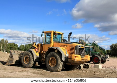 SALO, FINLAND-CIRCA SEPT. 2012:Loader and grapple tractor at construction site in Salo circa Sept.2012. After production shut down at Nokia Factory in Salo in autumn 2012, the future looks uncertain. - stock photo